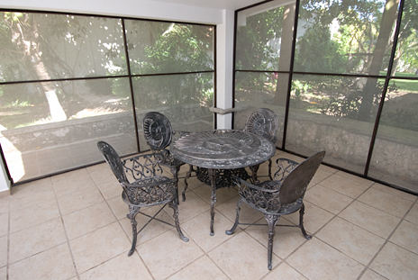 Screened patio is adjacent to the dining room and overlooks the pool area