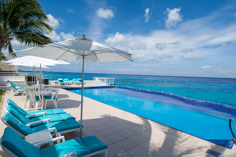 Poolside lounge chairs at Miramar vacation rental condos on the island of Cozumel Mexico