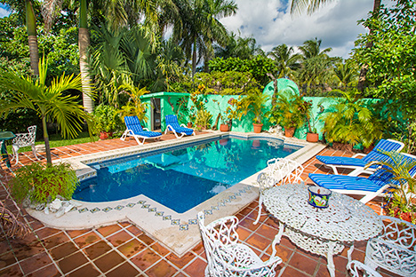 Poolside table has an umbrella to provide shade at Tres Palmas Cozumel vacation rental home